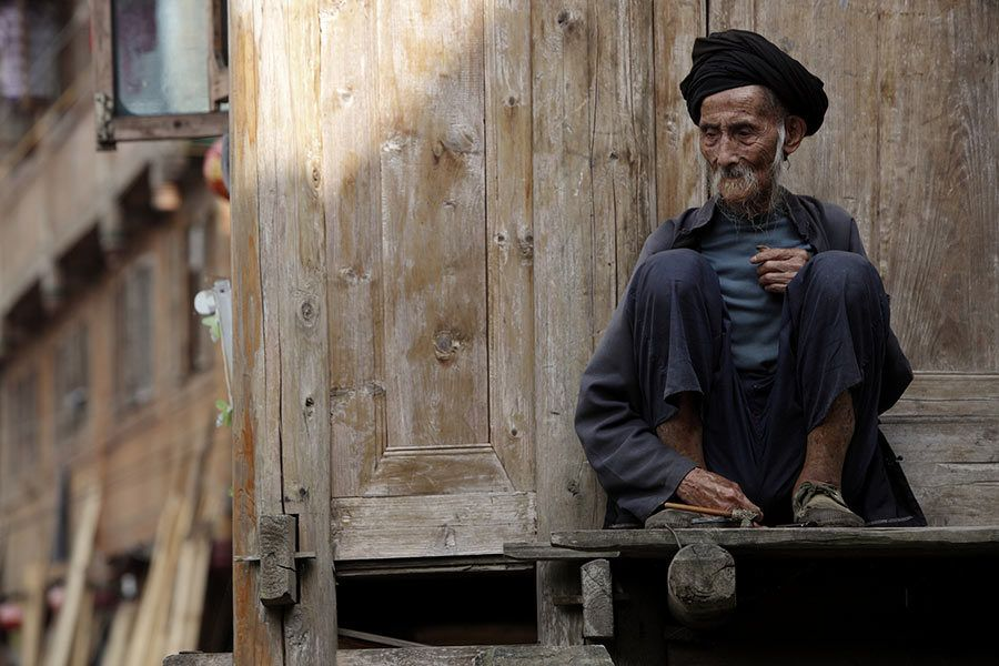 Elderly villager sitting at the door of his house in Zhong liu