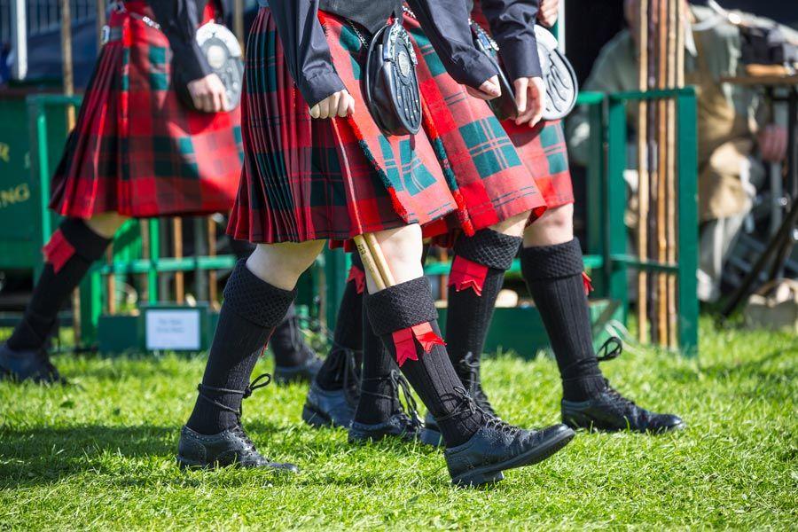 jovenes vestidos con kilt y ropa tradicional escocesa